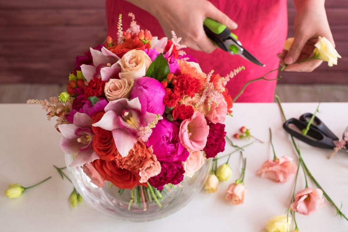 Women creating a flower arrangement with pink and red flowers